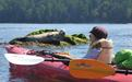 A young kayaker and a seal have a close encounter