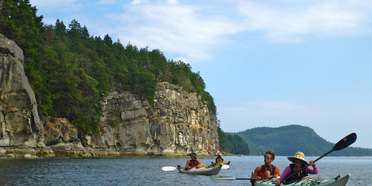 Kayakers paddle past cliffs of Valdes Island