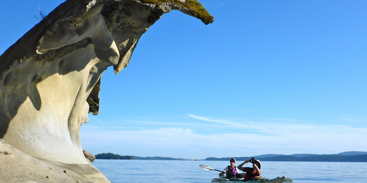 Kayakers paddle under sculpted sandstone overhang